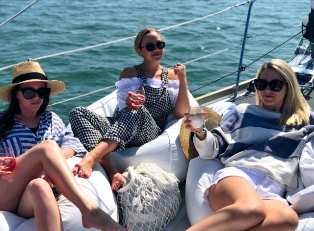 Three women sitting on beanbag chairs drinking wine on the bow of Layla
