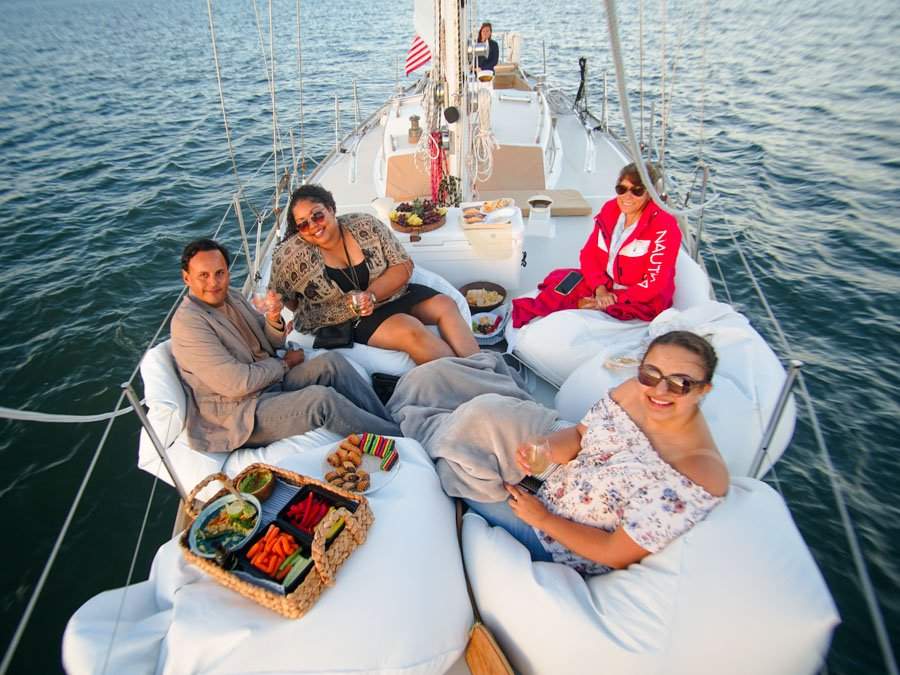Four people enjoying a food spread on the bow of Layla.