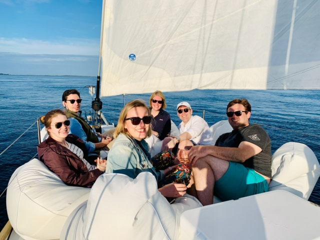 Six people sitting on the bow, drinking wine.