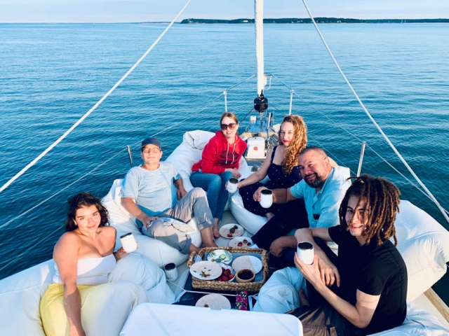 Six family members sitting on the bow with drinks and snacks.