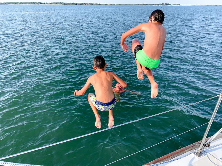 Two kids jumping off of Layla Sailing