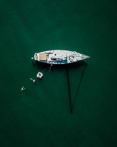 A drone shot of Layla from directly above with 3 people swimming in the water